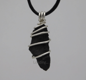 "N0184 Shungite Pendant Enamel Wire SKU: N0184 $64.00 16 gauge silver color enameled copper wire. Pendant is 1.5 inches in length. The Shungite sold on this site comes from the Zazhoginsky deposits in the Russian Republic of Karelia . We consider every piece of Shungite to be a sacred gift and we treat it as such. Please see the following blog for more information on Shungite. http://www.cosmicreality.net/shungite-blog/gaias-gift FREE Cord is made of cotton with a wax covering. 18"" long."